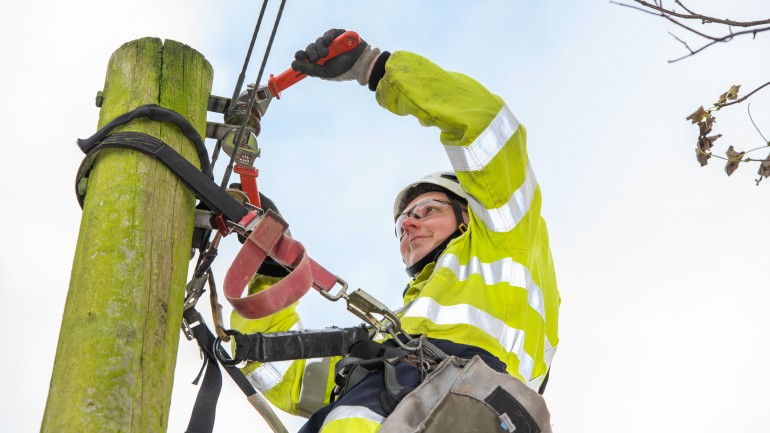 Electricity engineer climbing electrical pole